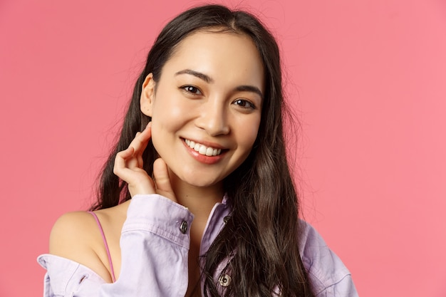 Close-up portrait of tender, beautiful young asian woman with clean skin, no pimples or blemishes, smiling lovely camera, touching neck and look camera romantic, stand pink wall