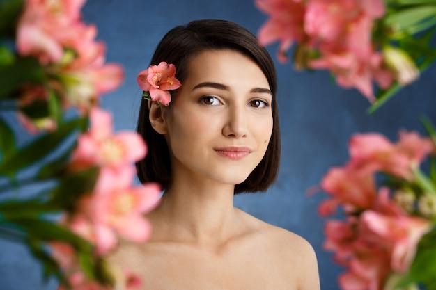 Chiuda sul ritratto di giovane donna tenera con i fiori rosa blured sopra la parete blu