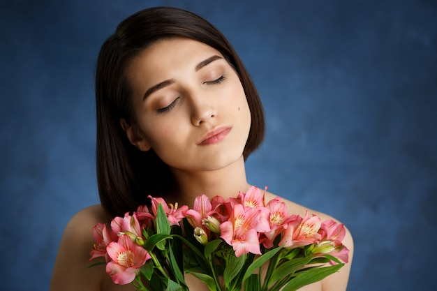 Close up portrait of tender  young woman with pink flowers over blue wall
