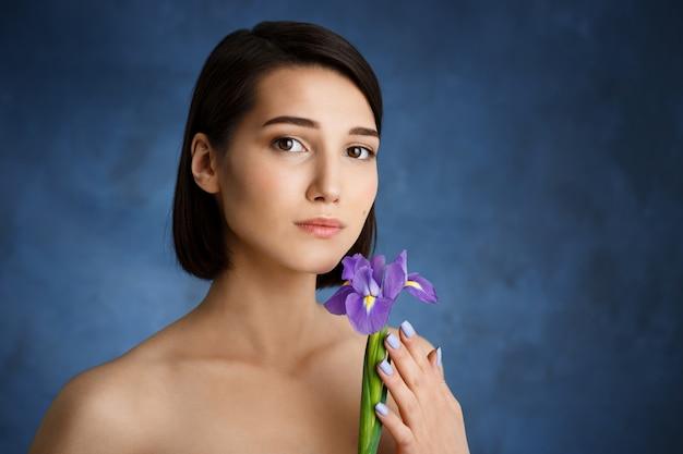 Chiuda sul ritratto di giovane donna tenera con l'iride viola sopra la parete blu