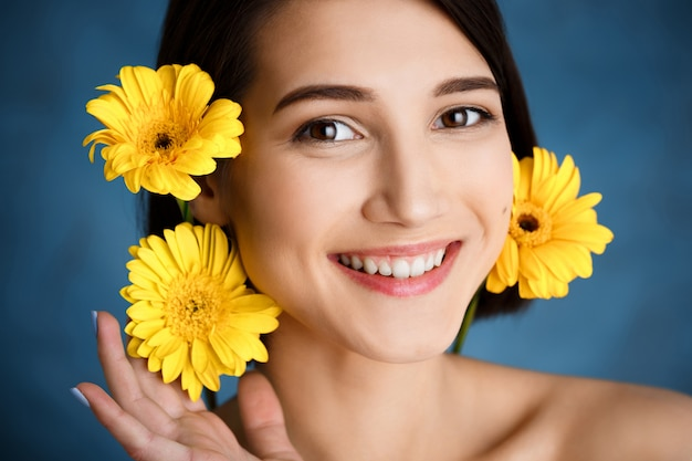 Close up portrait of tender  young woman with yellow flowers over blue wall
