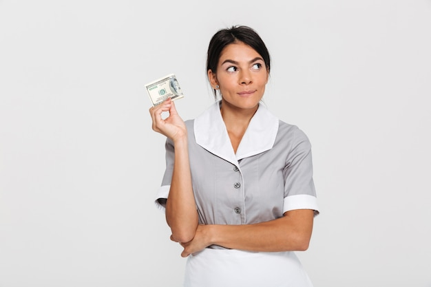 Close-up portrait of thinking pretty brunette woman in gray uniform holding dollar banknote and looking aside