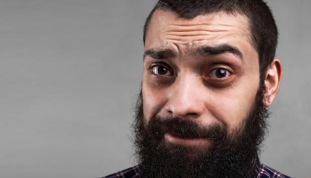 Close up ritratto di uomo barbuto stanco. faccia mattutina. hai bisogno di un caffè per alzarti presto. persona malata. concetto di problemi.