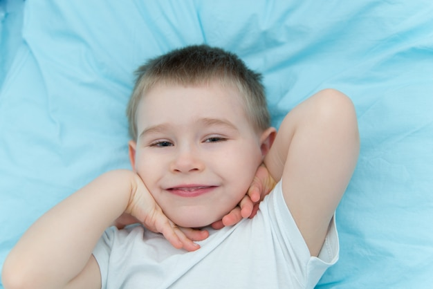 Close up portrait of the toddler boy laying in the bed