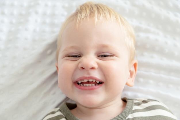 Закройте портрет мальчика малыша, улыбаясь с зубами кариеса.