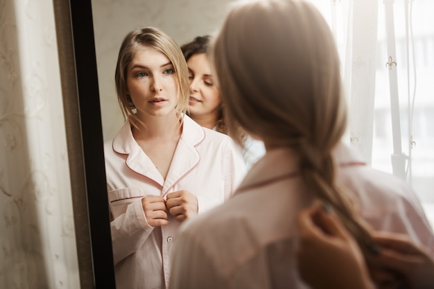 Close-up portrait of two beautiful women at home. attractive young blonde standing near mirror, changing clothes from pyjamas and waiting while mother combing braid. typical cozy morning in family