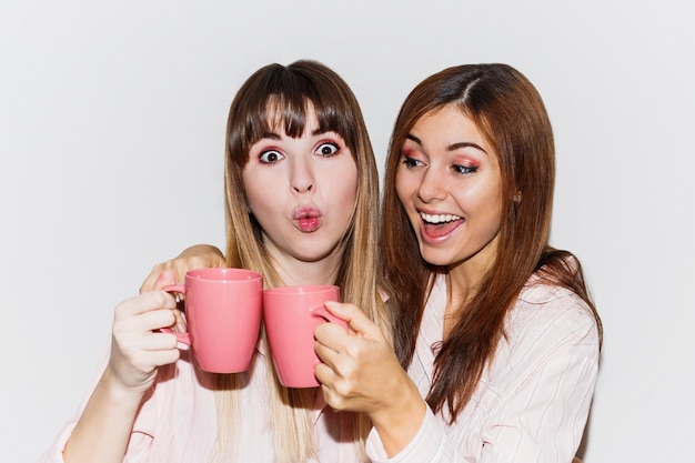 Close up portrait of two cheerful white  women in pink pajamas with cup of tea posing. flash portrait.