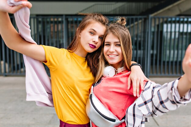 Ritratto del primo piano di due ragazze sognanti in abbigliamento estivo in posa con piacere davanti alla boutique di moda