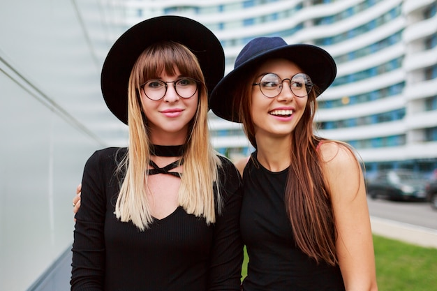 Close up portrait of two fashionable women embarrassing and walking together outdoor