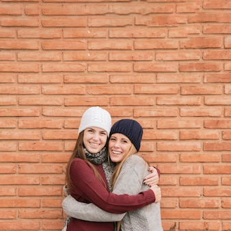 Close up portrait two hugging young women in front of brick wall