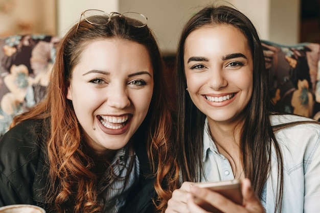 Close up portrait of two lovely female looking at camera laughing while holding a smartphone sitting in a cafe.