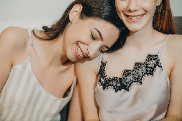 Close up portrait of a two lovely sisters laughing while having fun in pijama where brunette who is leaning head on her sister shoulder.