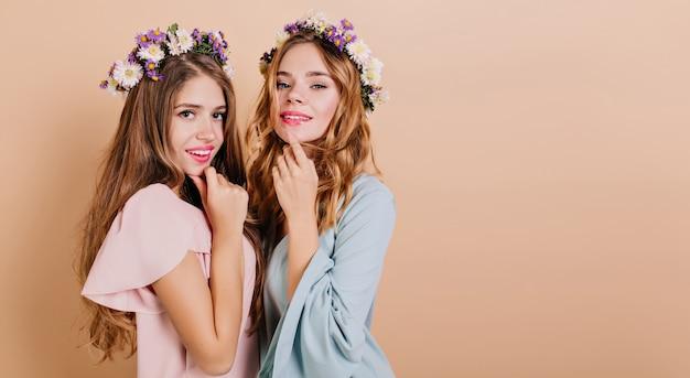 Ritratto del primo piano di due donne adorabili in abiti alla moda isolati su backround chiaro