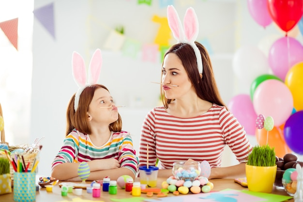 Close-up portrait of two nice attractive comic humorous playful cheerful girls small little pre-teen daughter wearing bunny ears holding pencil pout lips grimacing in white light interior room house