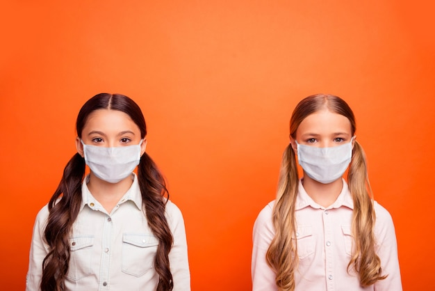 Close-up portrait of two nice attractive girls wearing safety mask stop influenza disease pandemia contamination china wuhan pneumonia isolated bright vivid shine vibrant orange color background