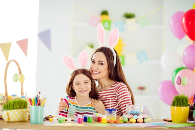 Close-up portrait of two nice attractive lovely charming cheerful cheery girls small little daughter wearing bunny ears making handicraft embracing in white light interior room house