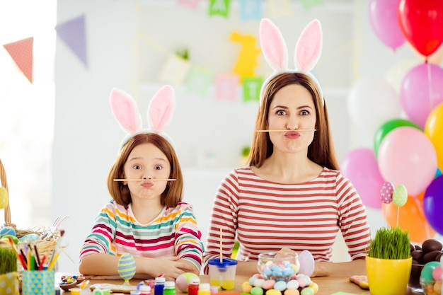 Close-up portrait of two nice attractive lovely comic childish cheerful cheery girls small little pre-teen daughter wearing bunny ears holding pencil pout lips in white light interior house