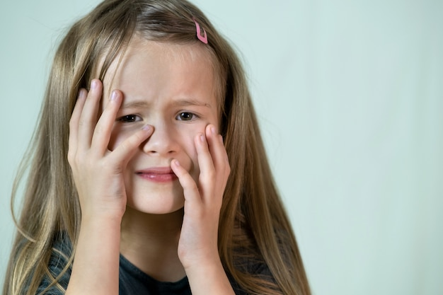 Close-up portrait of unhappy little girl with long hair covering her face with hands crying.