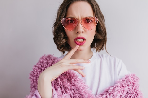 Close-up portrait of unpleased brunette woman in sunglasses making faces on white wall. indoor shot of fashionable caucasian girl in pink fur coat.