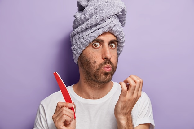 Close up portrait of unshaven young guy blows on nails, does manicure at home, holds nail file, care about his beauty and hygiene, wears bath towel and white t shirt, isolated on purple wall.