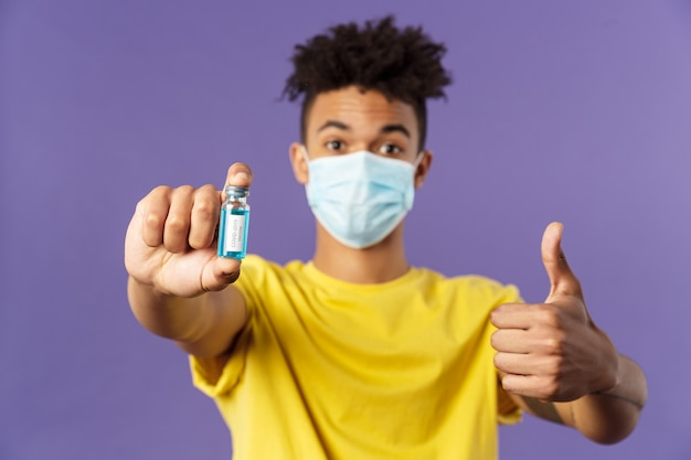Close-up portrait of upbeat young hispanic man in medical mask holding ampoule with coronavirus vaccine, coronavirus drug, show thumbs-up, getting shot at ambulance, standing purple background