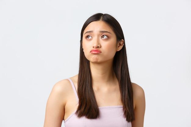 Ritratto del primo piano della bella ragazza asiatica cupa sconvolta p