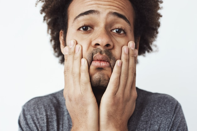 Close up portrait of upset and tired young african man grabing his face and cheeks with hands. hardworking student at the end of the day or victim of a car crash without insuranc