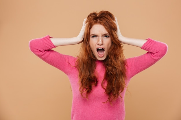 Close up portrait of an upset young redhead girl with her hands on her head and screaming