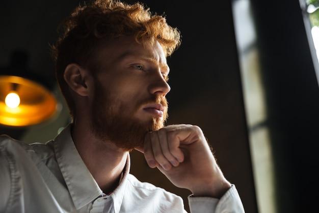 Ritratto del primo piano di giovane uomo arrabbiato di redhead che tiene il suo mento con la mano, guardante da parte