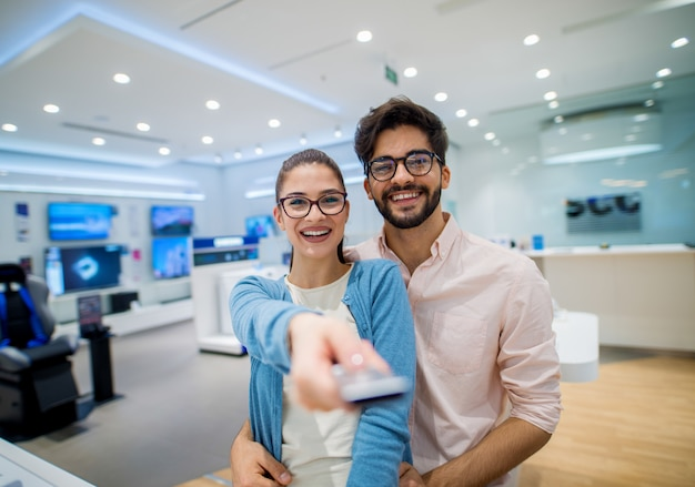 Close up portrait view of cute excited charming young student girl with eyeglasses holding tv remote control while her boyfriend hugging her in a tech store.