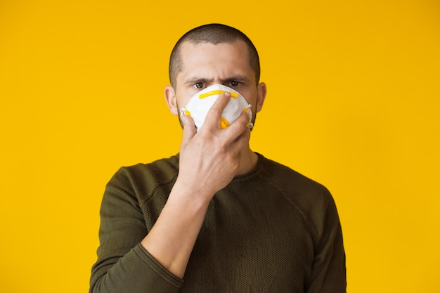 Close up portrait wearing a protective mask on a yellow wall