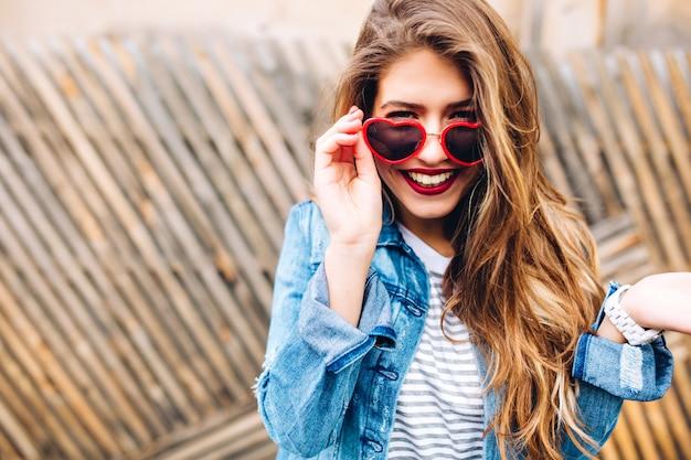 Ritratto del primo piano della ragazza sorridente europea bianca con capelli lunghi e labbra rosse. attraente giovane donna che ride ha lasciato cadere gli occhiali da sole alla moda in sorpresa sullo sfondo sfocato.