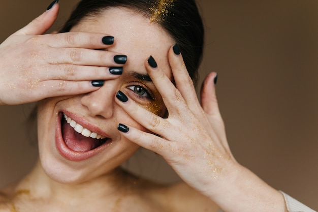 Close-up portrait of white young lady playfully posing. joyful girl with black manicure laughing