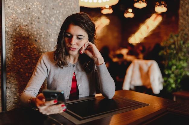 Портрет крупным планом с кавказской довольно молодой женщиной, держащей смартфон, сидя в ресторане.