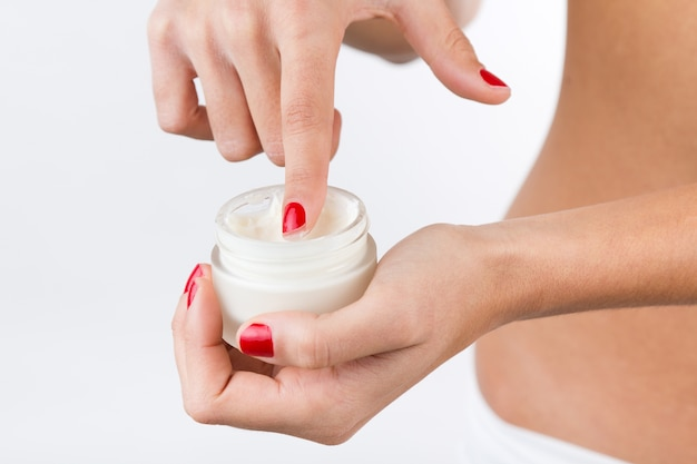 Close up portrait of woman applying cream on hands