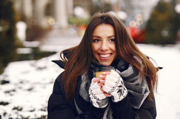 Close-up ritratto di donna in giacca nera, bere il caffè
