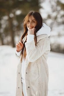 Close-up ritratto di donna in giacca nera. donna in piedi in una foresta in una giornata nevosa.