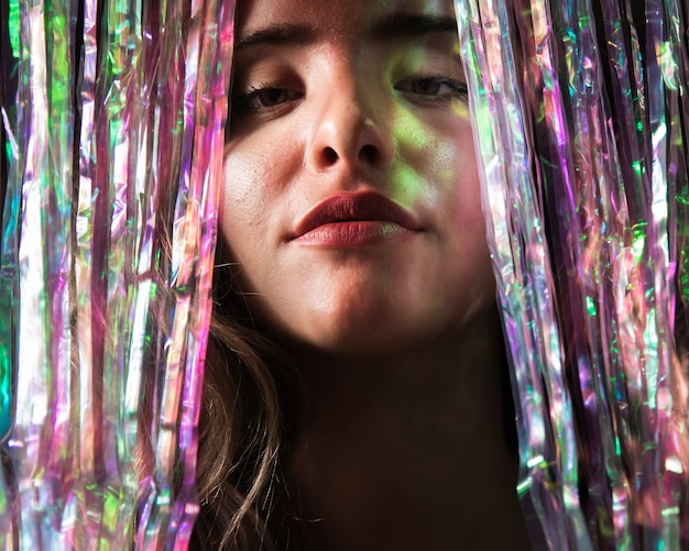 Close-up portrait of woman and curtain of sparkles