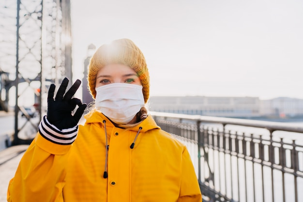 Close up portrait of woman dressed in yellow windbreaker outdoor in protective surgical mask on her face and gloves shows sign ok with hope that everything will be fine. coronavirus pandemic concept