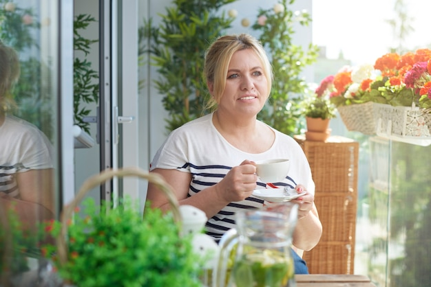 Close up portrait of woman drinking coffee on the balcony