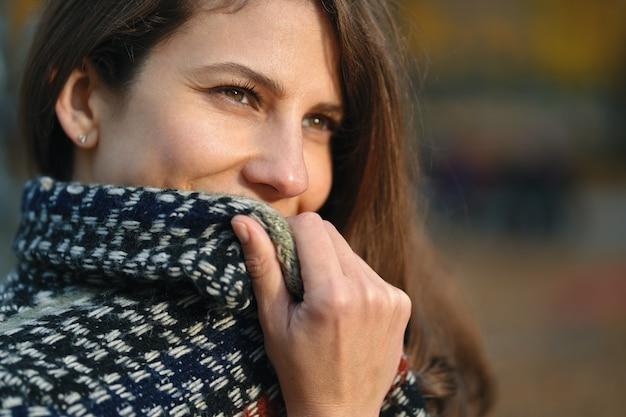 クローズアップの肖像画、隠れている女性、コートの襟の後ろの笑顔。ナチュラルブラウンのウェーブのかかった髪と目