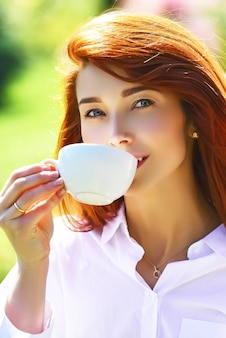 Close up portrait of a woman holding a hot coffee cup outdoors on the spring background red head gir...