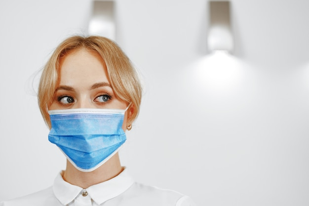 Close up portrait of woman hotel receptionist wearing medical face mask