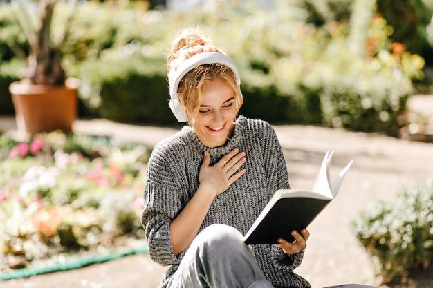 Ritratto del primo piano della donna che ascolta la musica e che legge un libro