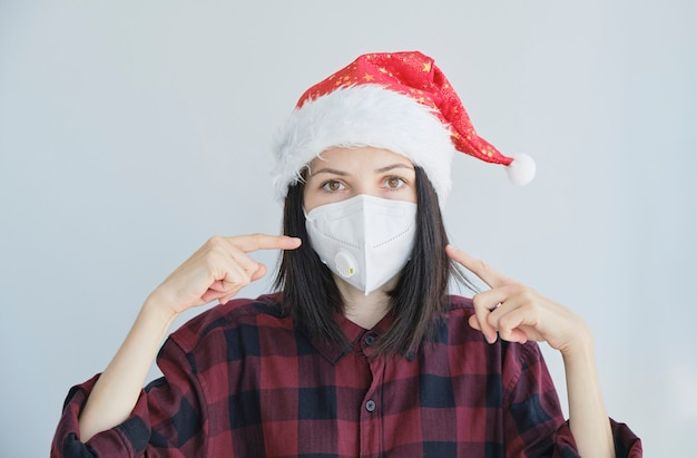 Close up portrait of woman in medical, disposable mask and christmas red cap