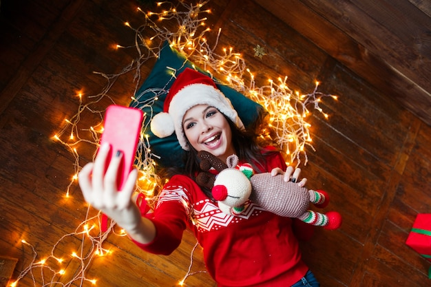 Close-up portrait of woman in santa hat wrapped in christmas lights taking selfie and lying on wooden floor at home