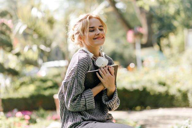 Close-up ritratto di donna seduta in serra con le cuffie e il libro
