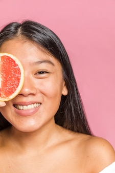 Close-up portrait of woman smiling and a grapefruit