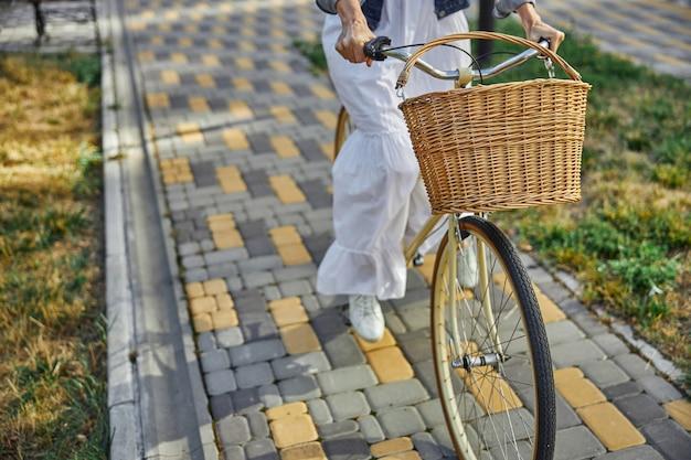 그림 같은 햇살 가득한 거리에서 시간을 보내는 동안 바구니와 함께 자전거로 생태 교통을 사용하는 초상화 여성을 닫습니다
