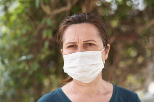 Close up portrait of woman wearing surgical mask because of viruses and air pollution.